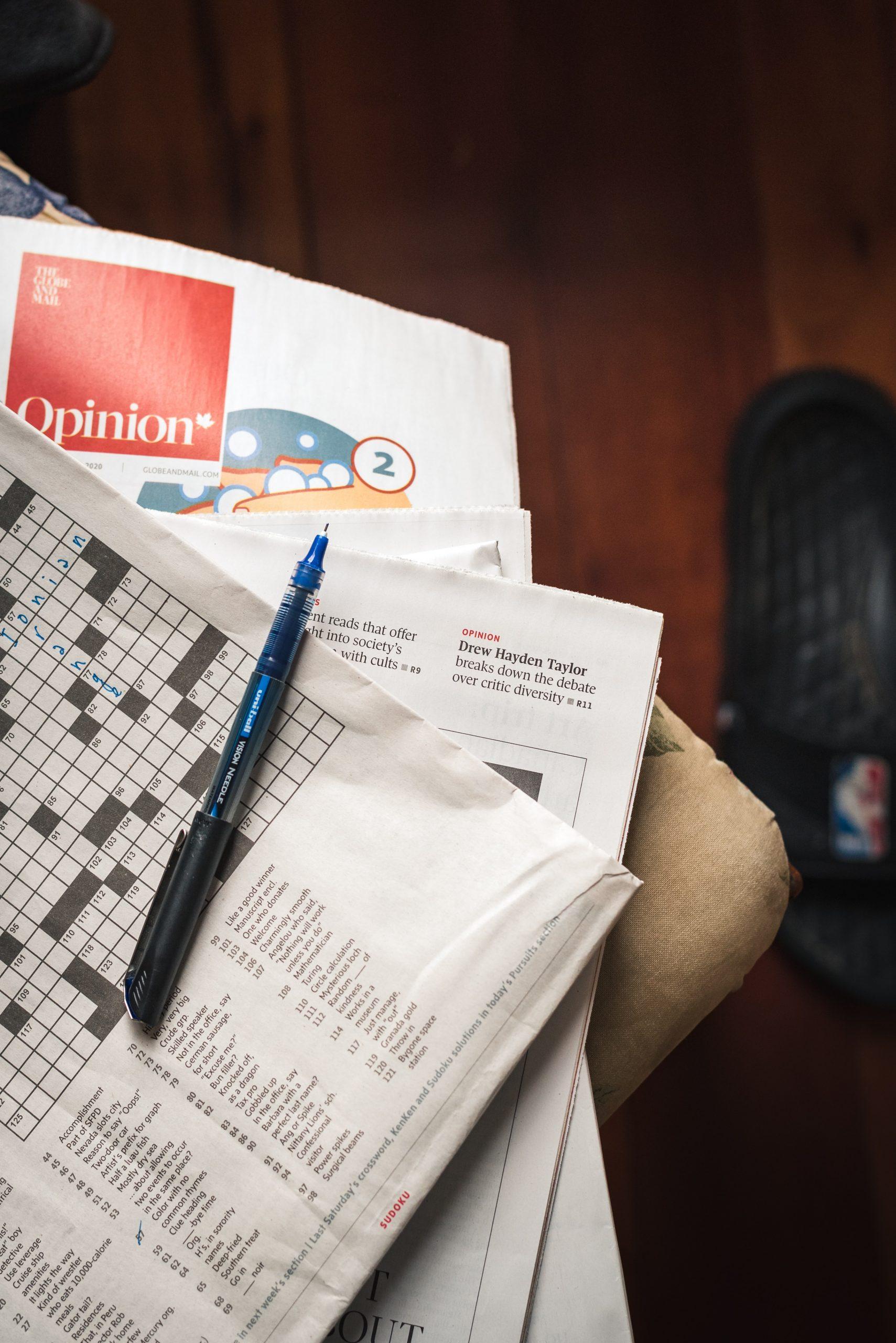 pen lying across a crossword puzzle